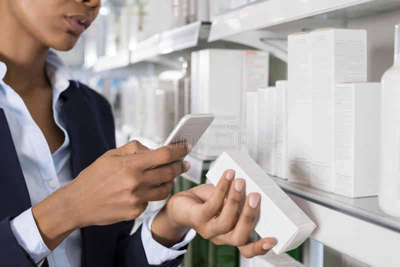 Businesswoman Scanning Barcode Through Smart Phone. Cropped image businesswoman scanning barcode through smart phone in pharmacy royalty free stock photography