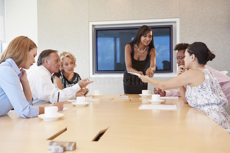Businesswoman By Screen Addressing Boardroom Meeting royalty free stock photography