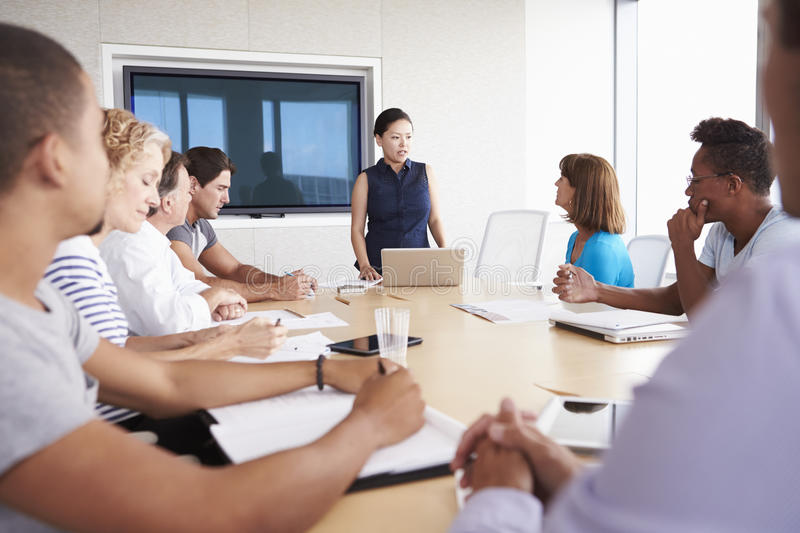 Businesswoman By Screen Addressing Boardroom Meeting royalty free stock image