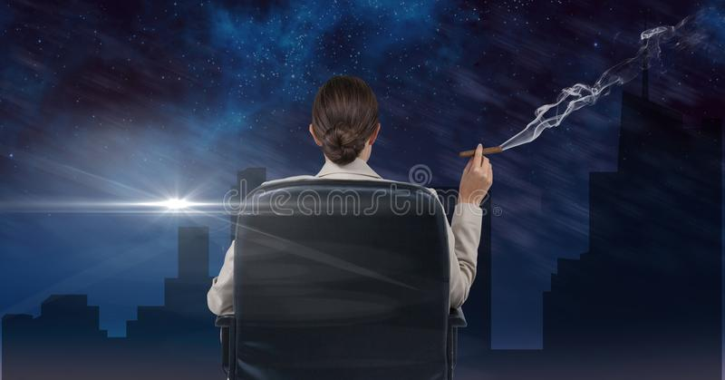 Businesswoman seated in a chair smoking and watching the town during the night. Digital composite of Businesswoman seated in a chair smoking and watching the royalty free stock image