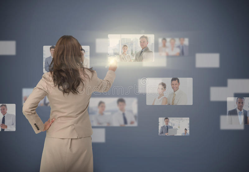 Businesswoman selecting digital interface. Showing coworkers royalty free stock image