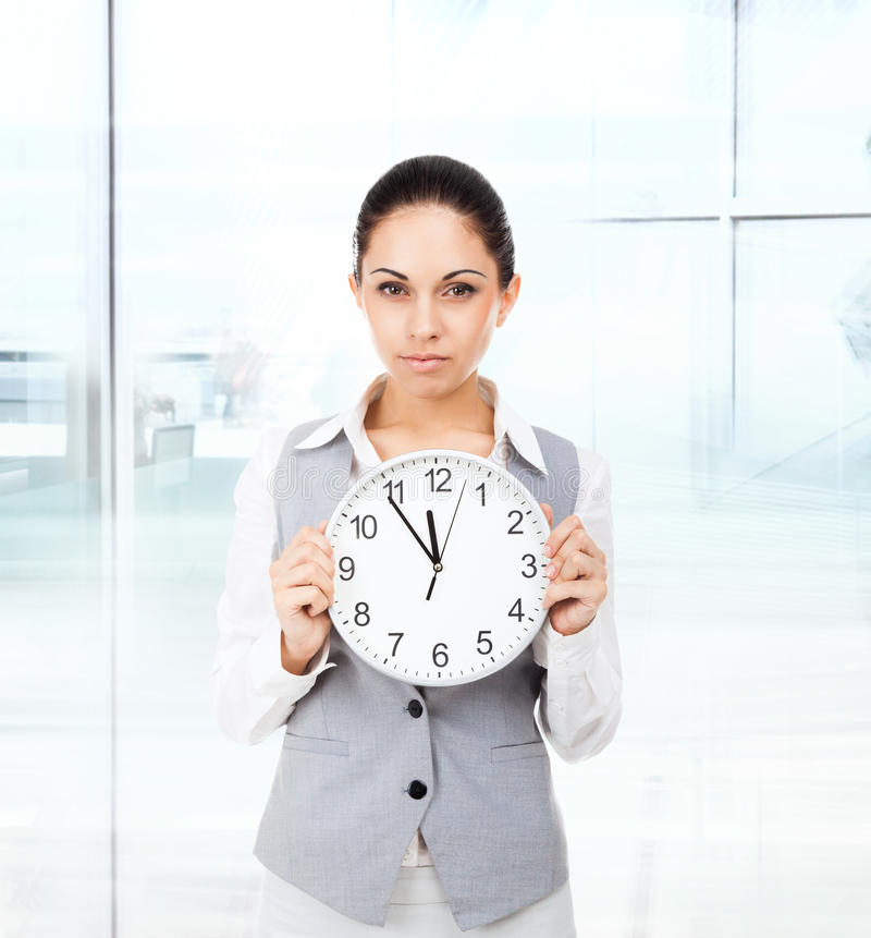 Businesswoman serious, hold clock. Young attractive business woman stock image