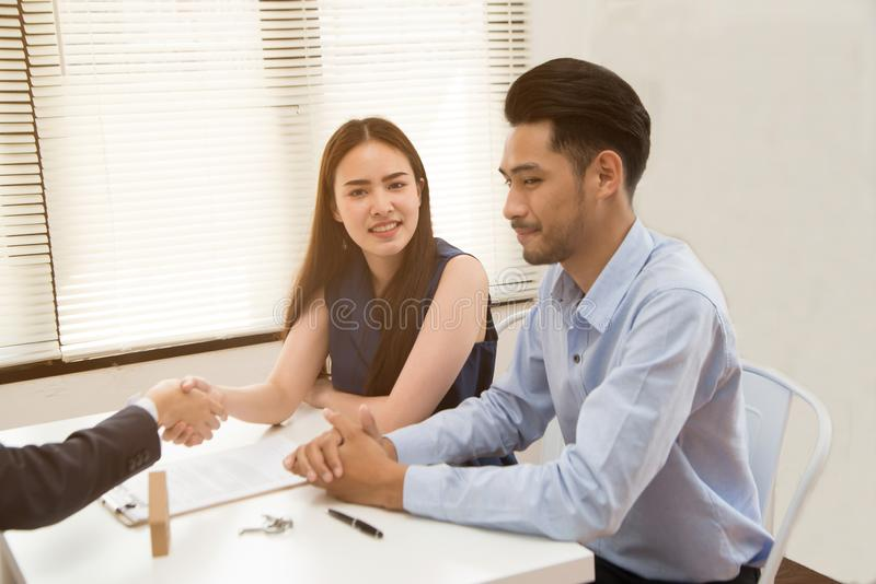 Asian female salesman sit in a modern office room and talk to customers and be satisfied with success. Businesswoman shaking hand with a young couple in office stock photo