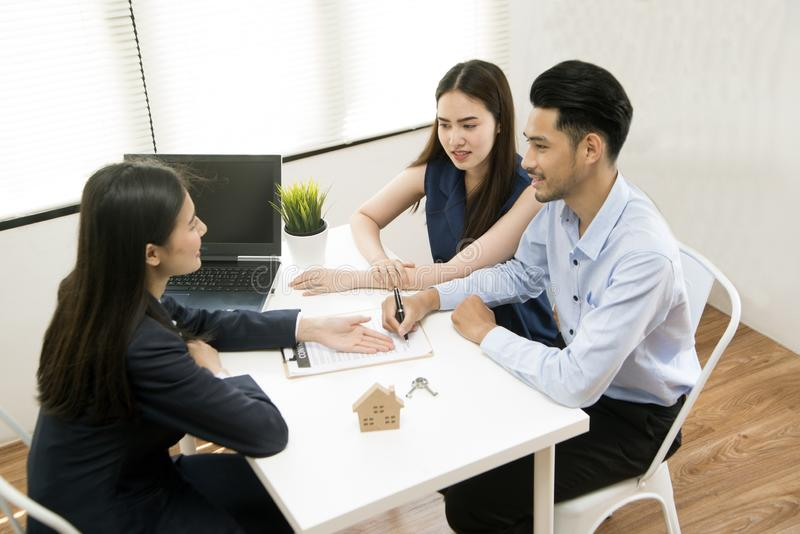 Asian female salesman sit in a modern office room and talk to customers and be satisfied with success. Businesswoman shaking hand with a young couple in office stock photos