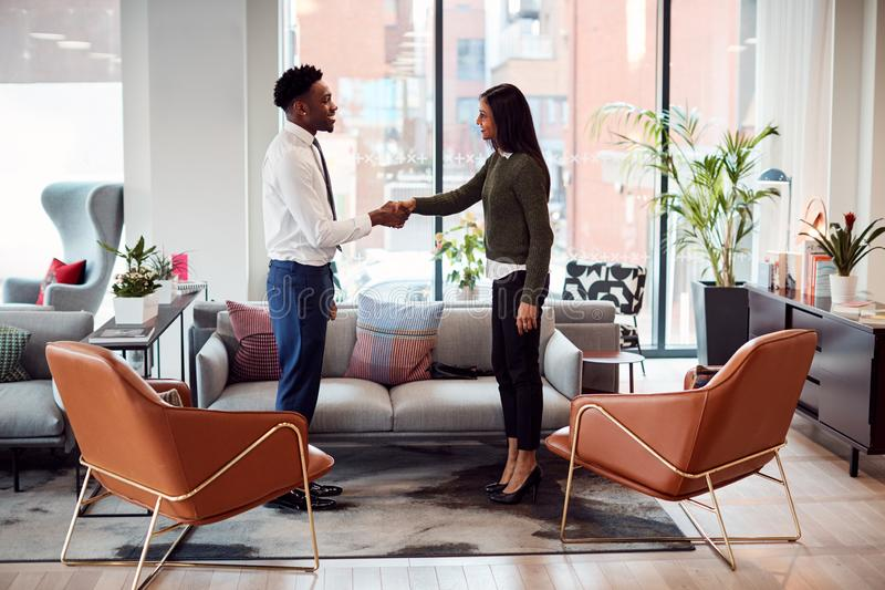Businesswoman Shaking Hands With Male Interview Candidate In Seating Area Of Modern Office stock image