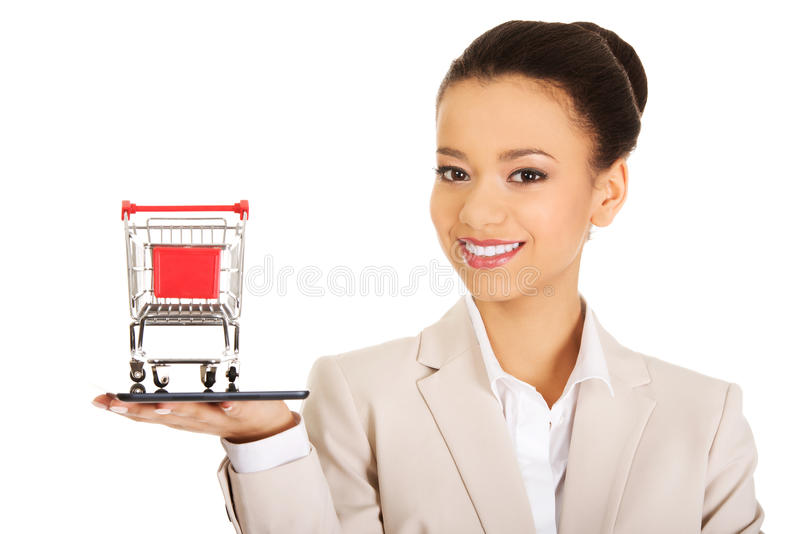 Businesswoman with shopping cart and tablet. stock photography
