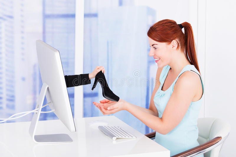 Businesswoman shopping shoes online at computer desk. Side view of young businesswoman shopping shoes online at computer desk royalty free stock images