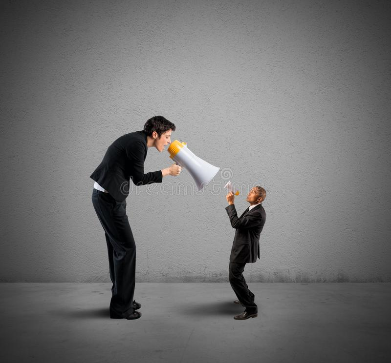 Businesswoman shouting through a megaphone. Businesswoman shouting a businessman through a megaphone royalty free stock photography