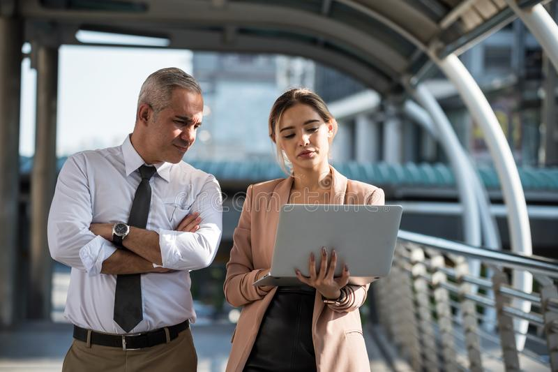 Businesswoman show project plan in computer to boss stock image