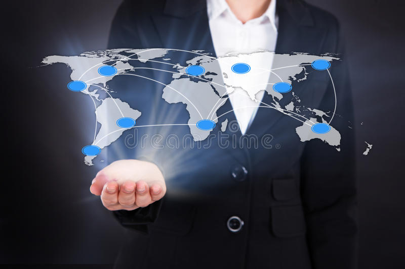 Businesswoman Showing Connected World Map. Digital composite image of businesswoman showing connected world map representing globalization. Source of reference stock photo