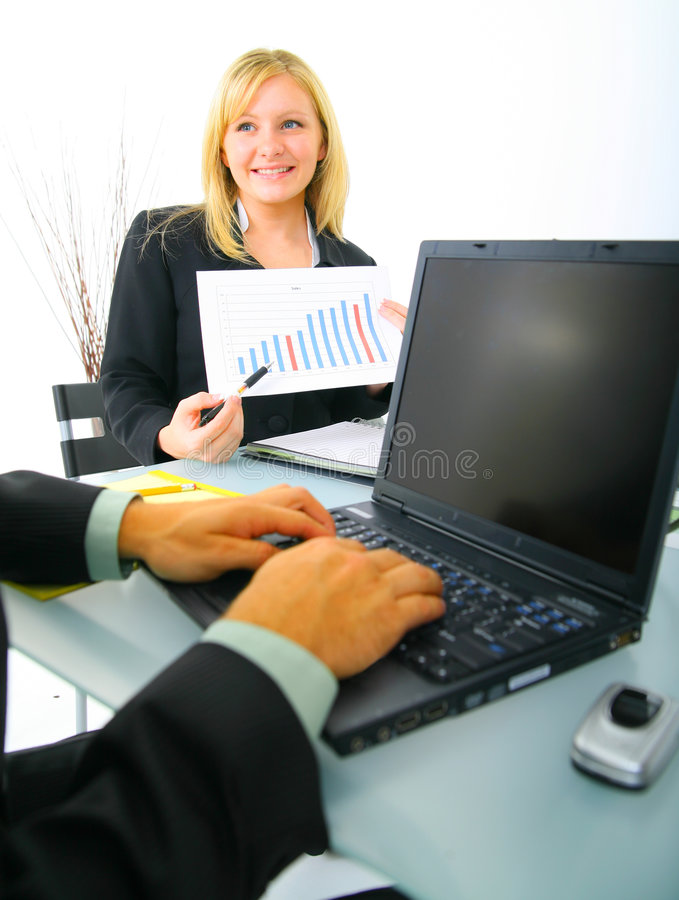 Businesswoman Showing Financial Chart. To other coworker. focus on the blond caucasian woman stock photo