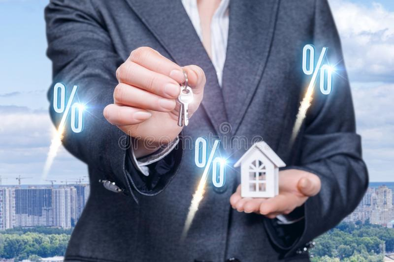 A businesswoman showing keys and holding a house model on her palm royalty free stock images