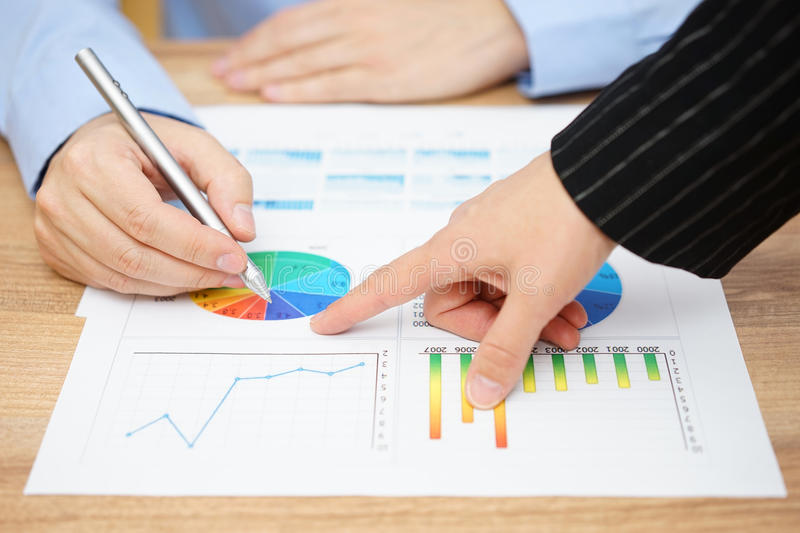 Businesswoman showing sales report to his client stock photography