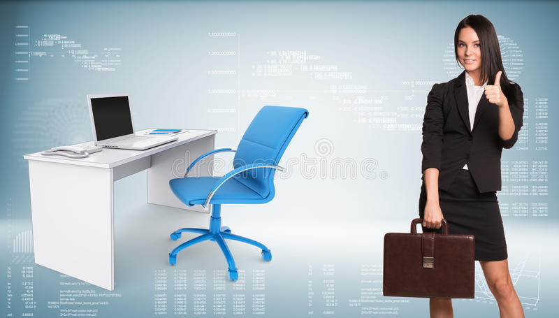 Businesswoman showing thumb-up. Office table with. Businesswoman in suit holding briefcase and showing thumb-up. Office table with chair and open laptop are royalty free stock photo