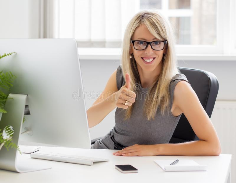 Businesswoman showing thumbs up gesture while sitting at desk. Young smiling businesswoman showing thumbs up gesture while sitting at desk royalty free stock images