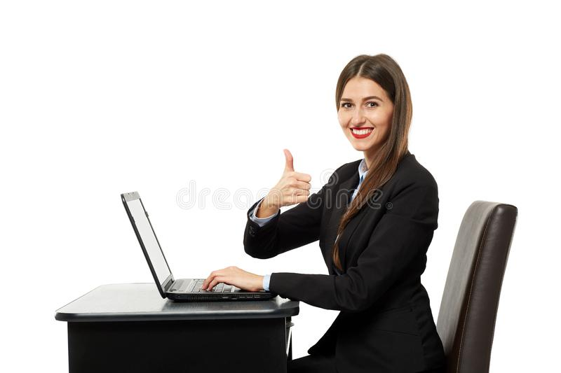 Businesswoman showing thumbs up sign. Happy businesswoman showing thumbs up sign sitting at her laptop royalty free stock image