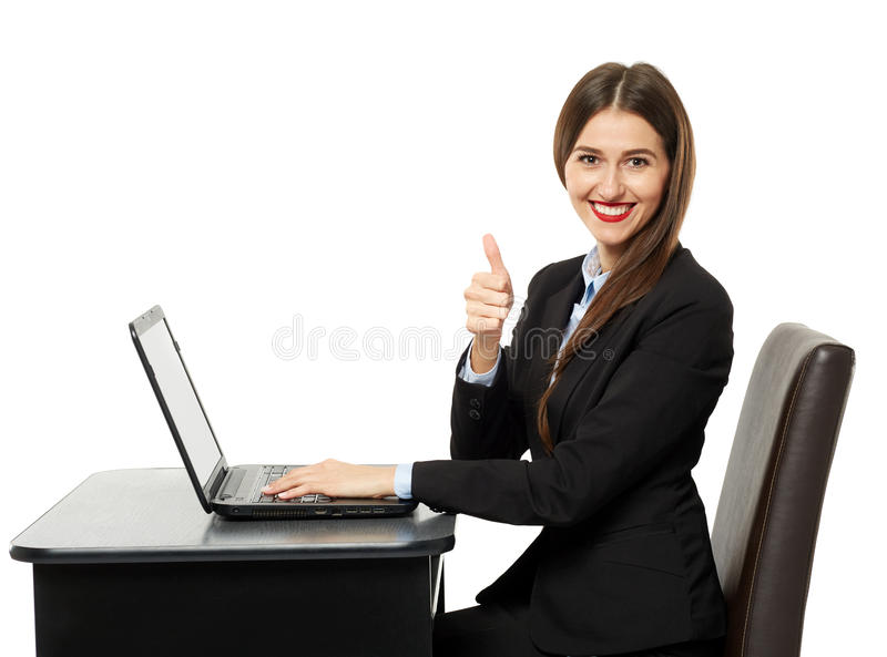 Businesswoman showing thumbs up sign. Happy businesswoman showing thumbs up sign sitting at her laptop stock photos