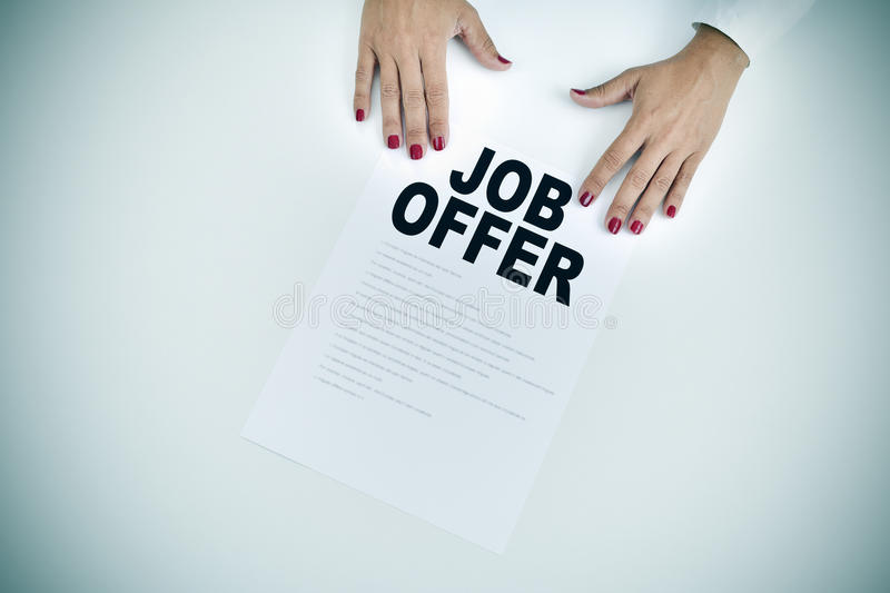 Businesswoman shows a document with the text job offer. High-angle shot of the hands of a businesswoman with a document with the text job offer at an office desk stock images