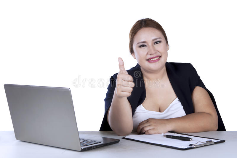 Businesswoman shows ok sign with thumb. Businesswoman showing ok sign with her thumb while sitting in front of her laptop, isolated on white background stock photography