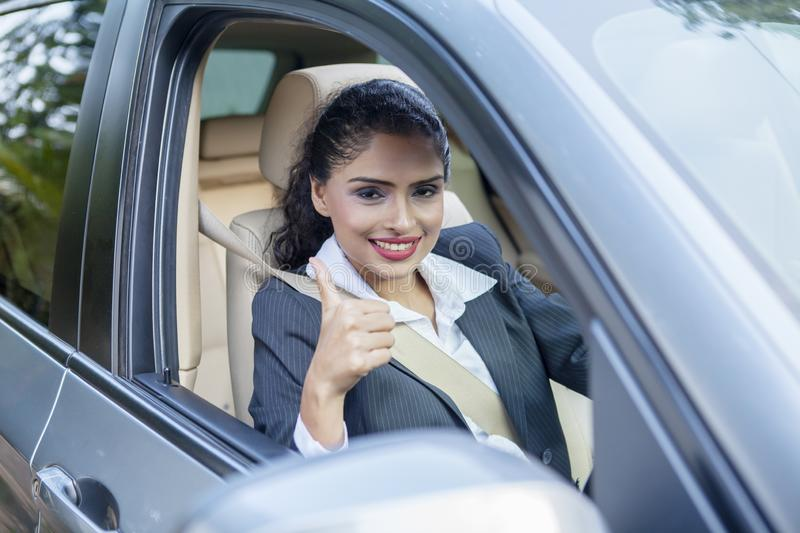 Businesswoman shows thumb up inside the car stock image