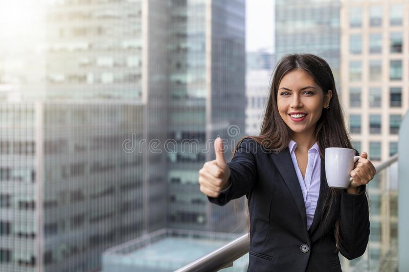 Businesswoman shows the thumbs up in front of modern office buildings in the city. Attractive businesswoman in corporate outfit shows the thumbs up with her stock photography