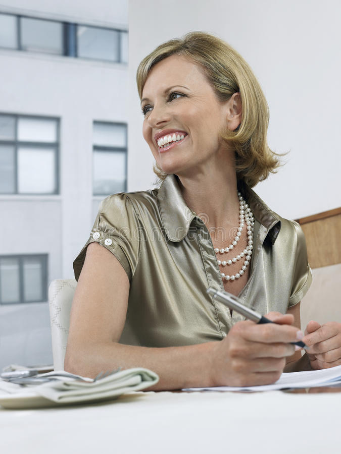 Businesswoman Signing Contract In Restaurant royalty free stock image