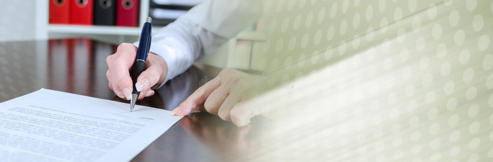 Businesswoman signing a document; panoramic banner stock photo