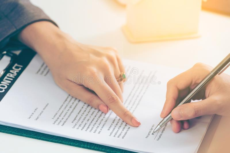 Businesswoman signs agreement contract in office stock images