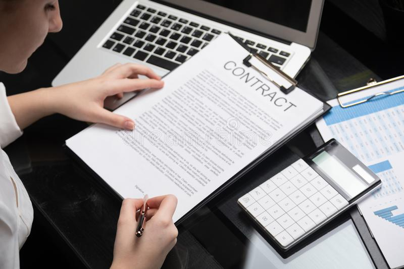Employee gets acquainted with contract in stylish office royalty free stock image