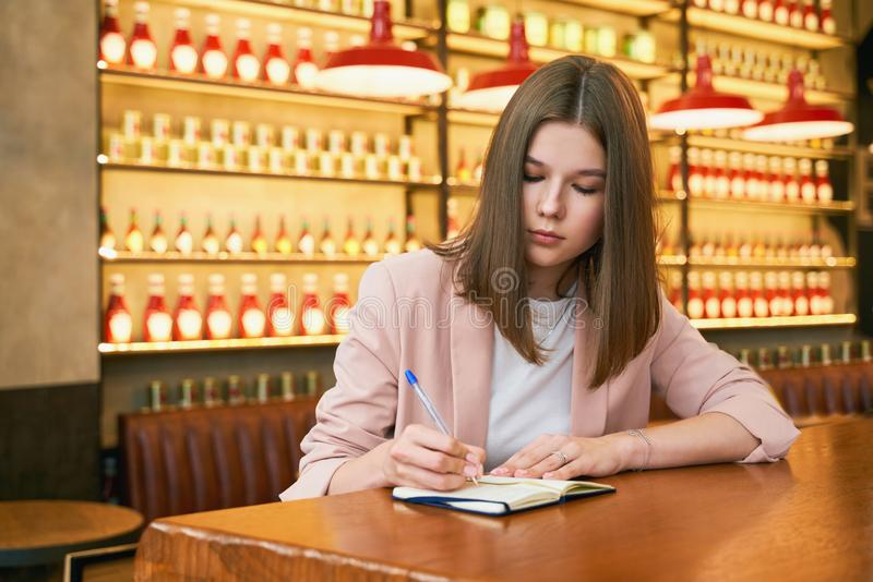 Businesswoman sit at table in cafe with notebook royalty free stock image