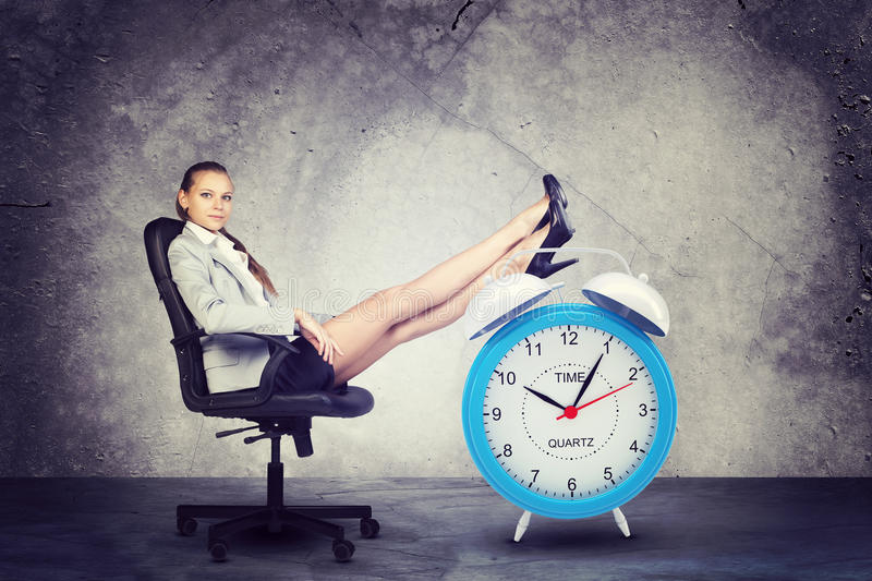 Businesswoman sits in chair. Put your feet up on royalty free stock photography