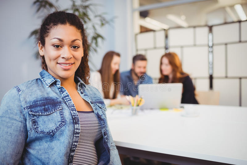 Businesswoman sitting against coworkers in meeting room. Portrait of smiling businesswoman sitting against coworkers in meeting room stock photos