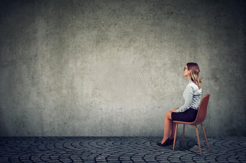 Business woman sitting on a chair in front of a wall and thinking stock photo