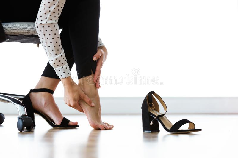 Businesswoman sitting on a chair and massaging her hurting toes after wearing every day heels. stock photography