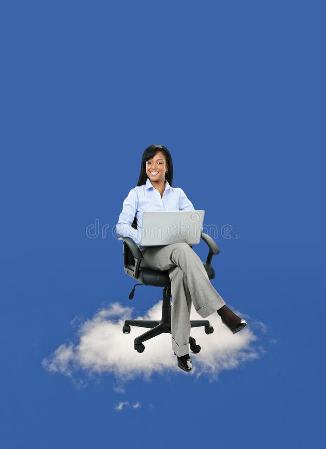 Businesswoman sitting on cloud with computer stock images