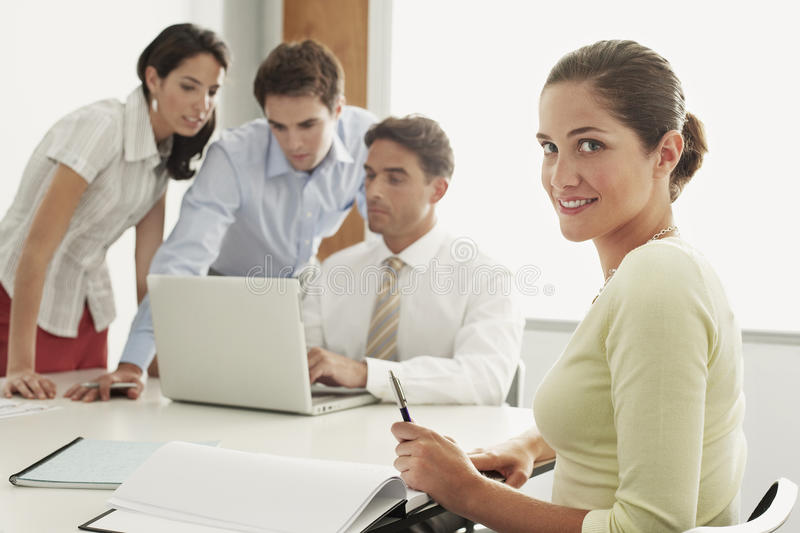 Businesswoman Sitting With Colleagues Working On Laptop At Desk stock image