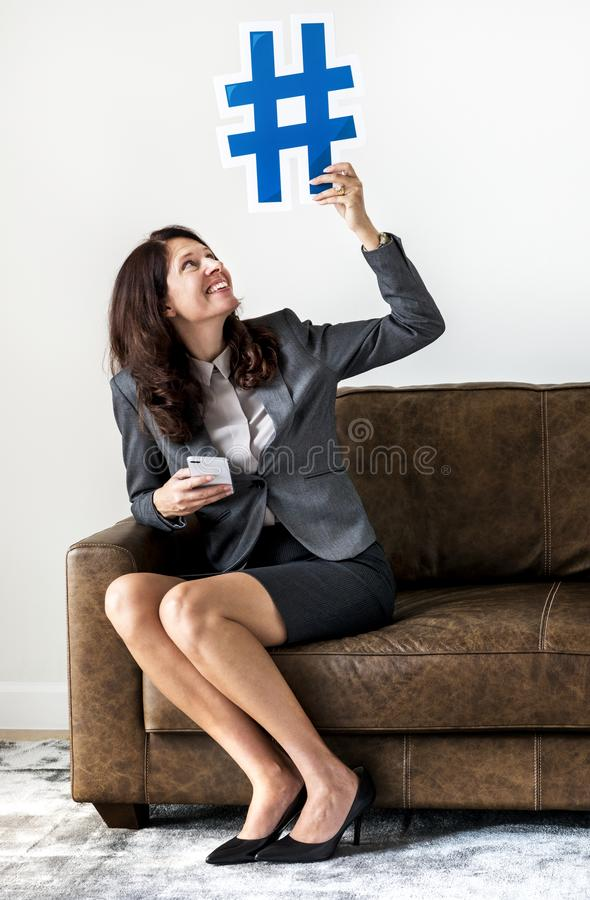 Businesswoman sitting on couch holding icon royalty free stock images