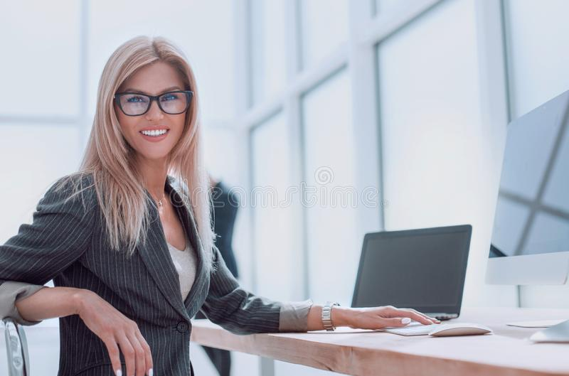 Businesswoman sitting at her Desk and looking at the camera. Photo with copy space stock image