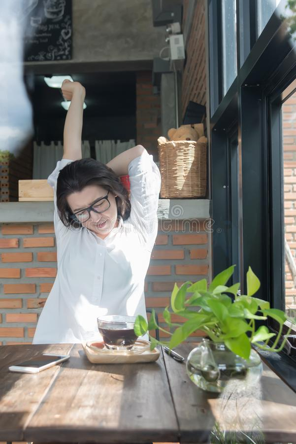 Businesswoman sitting at her work place and stretching her hands above her head.Tired female employee at workplace in front of. Glass of coffee stock image