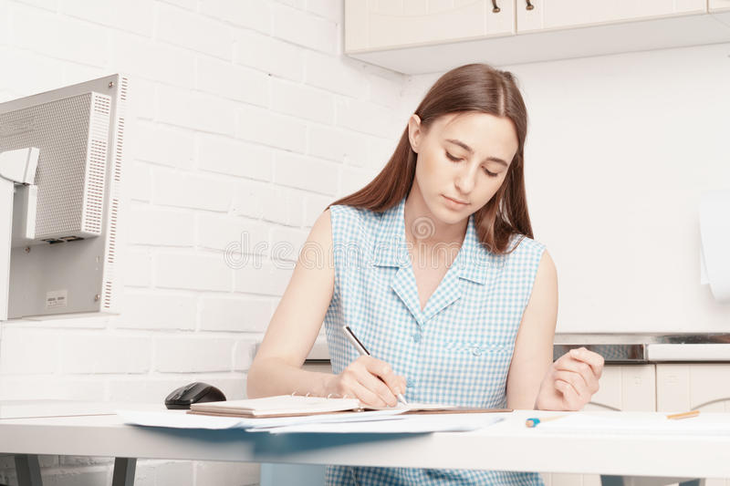 Businesswoman is sitting at his desk and writing in a notebook. stock image