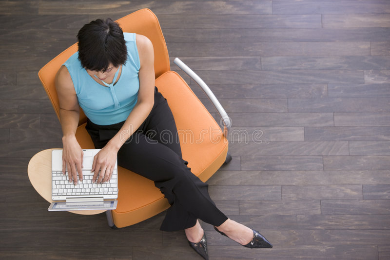 Businesswoman sitting indoors with laptop stock photo
