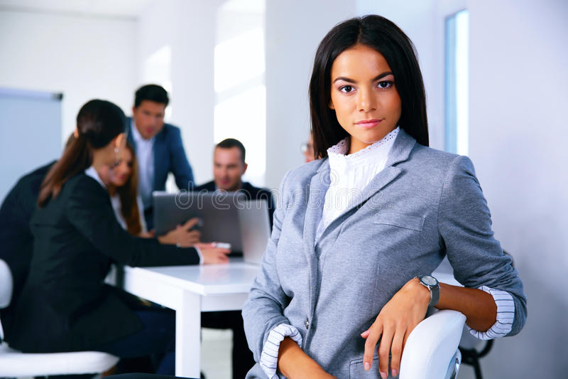 Businesswoman sitting on the office chair. In front of business meeting stock images