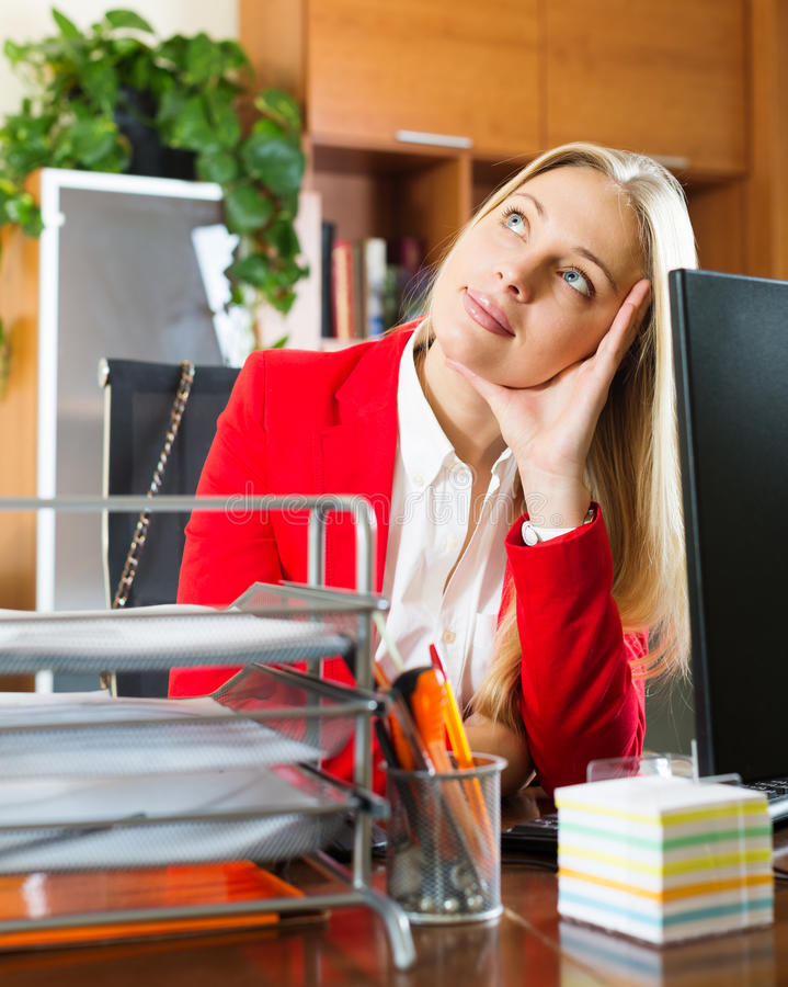 Businesswoman sitting at office desk and dreaming. Bored businesswoman in red sitting at office desk and dreaming stock photo
