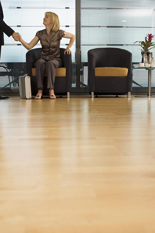 Businesswoman sitting in office reception area, shaking hands with businessman, surface level royalty free stock images