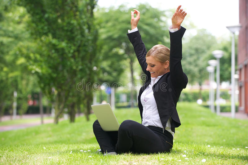 Businesswoman sitting outdoors with laptop and arms up in celebration stock photo