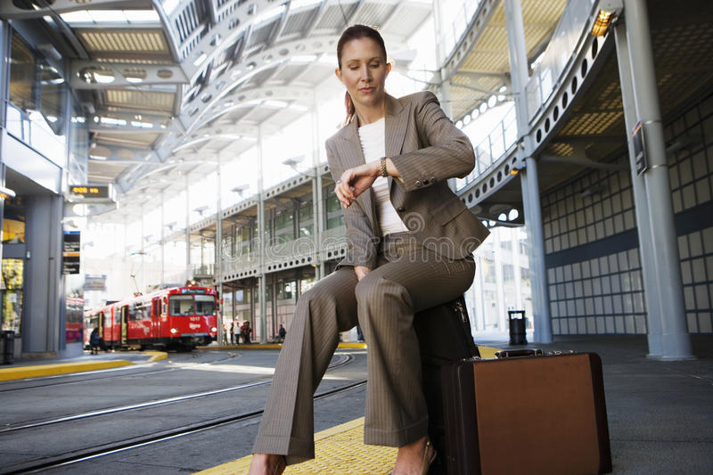 Businesswoman sitting on suitcase, waiting for city tram, checking time on wristwatch (surface level) royalty free stock photo