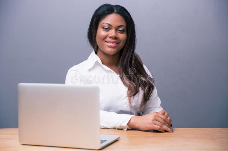 Businesswoman sitting at the table with laptop stock photo