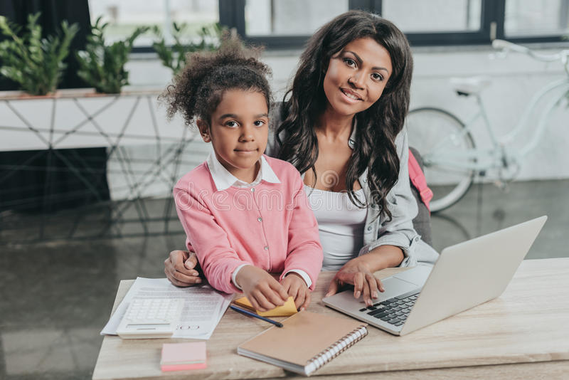 Businesswoman sitting at workplace with daughter and looking at camera. Smiling businesswoman sitting at workplace with daughter and looking at camera royalty free stock photos