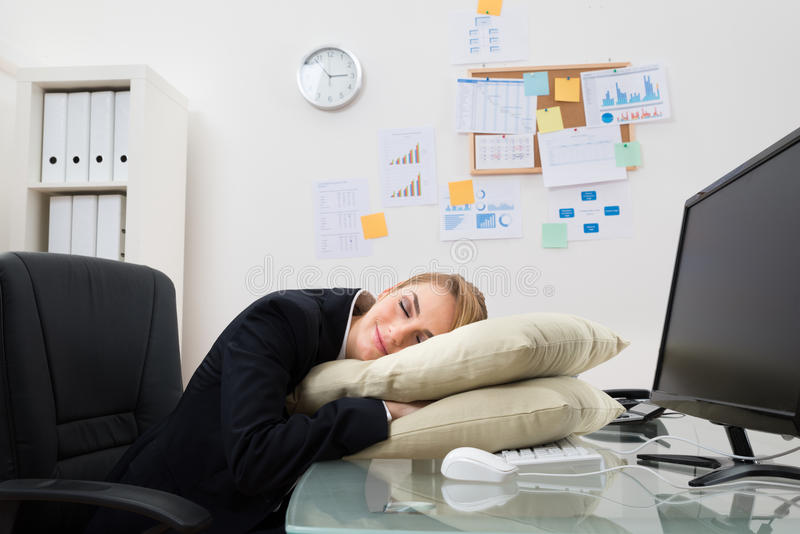 Businesswoman sleeping in office stock photo
