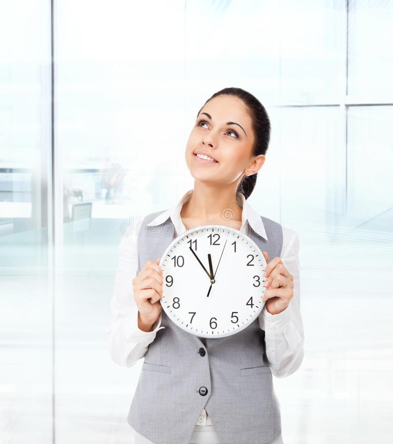 Businesswoman smile hold clock think look up stock photography